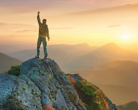 Young man on rock on top of a mountain holding up his fist